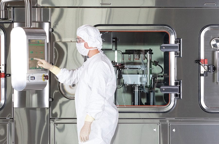 Operator working with a Vanrx SA25 Aseptic Filling Workcell, which can fill commercial and clinical drug products into vials, syringes and cartridges.